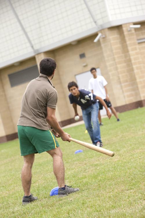 Студенты играют в бейсбол на территории школы