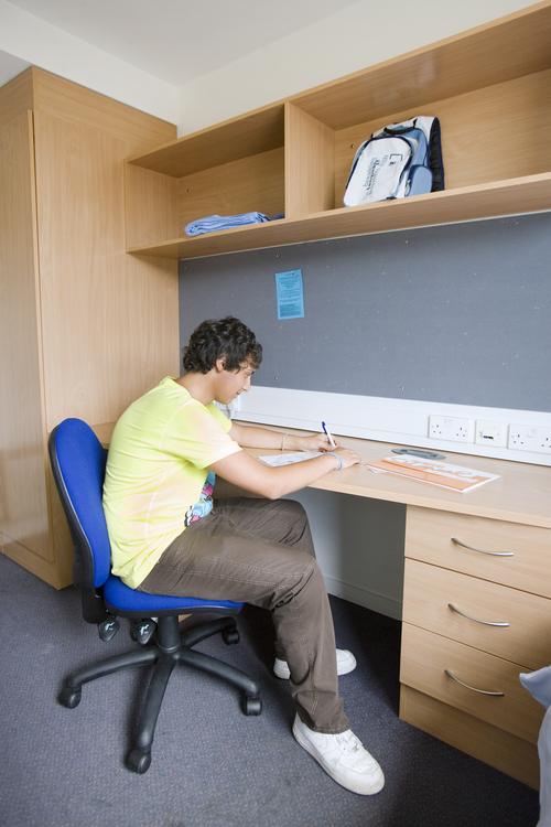 Студент занимается в своей комнате после занятий